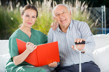 Confident Female Nurse And Senior Man With Book