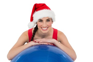Festive fit brunette leaning on exercise ball