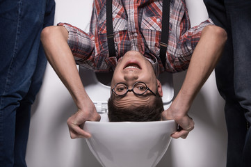 man is standing upside down on toilet bowl.