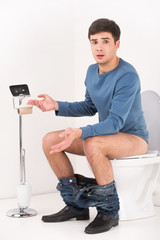 Young handsome man sitting on toilet