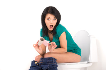 beautiful brunette girl sitting on toilet seat.
