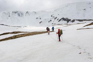 Group of hikers in winter mountains on cloudy day