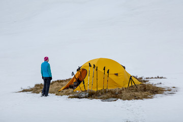Hikers set oragne tent in winter mountains on cloudy day