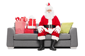 Santa sitting on a couch full of Christmas presents