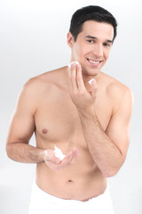 Closeup of young man shaving isolated on white background.