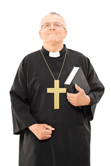 Mature priest holding a bible and looking up