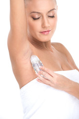 woman applying deodorant in armpit on white background.
