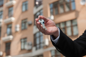 Human hand holding key to dream house isolated