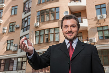 adult man holding key to dream house isolated