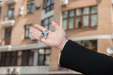 real estate concept with silver keys in fingers with building.