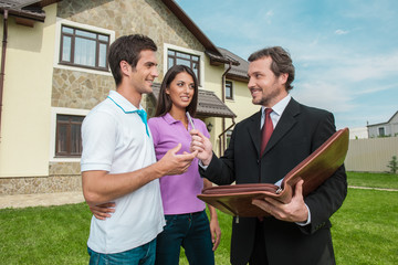 Young couple signing renting contract with real estate agent.
