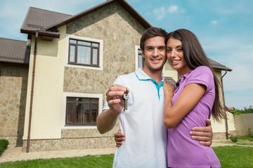 Couple in front of new home holding door keys.