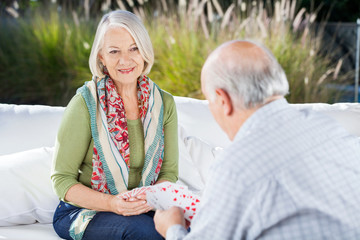 Happy Senior Woman Playing Cards With Man