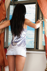 long-haired woman in nightgown looking out the window