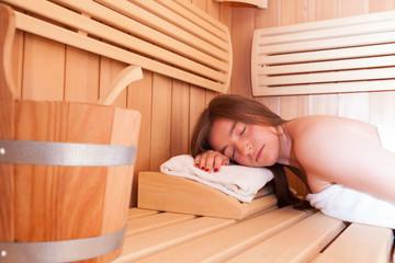 Caucasian young woman enjoying sauna.