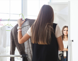 Portrait of attractive teen girl making choices clothes at home
