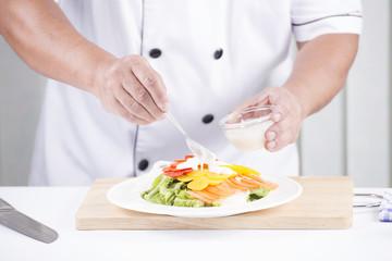 Chief putting salad dressing