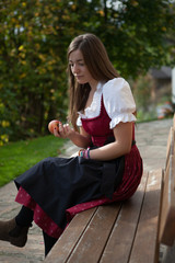 Young woman sitting in the autum sun outside on a bench