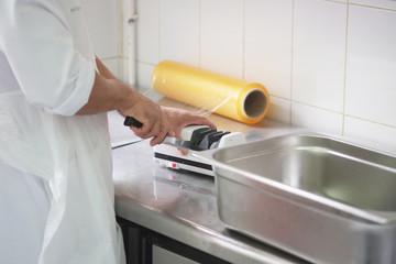 cook sharpens a knife