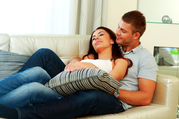 Young beautiful couple relaxing on the sofa at home