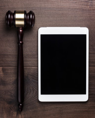judge gavel and tablet computer on brown wooden backgroundjudge