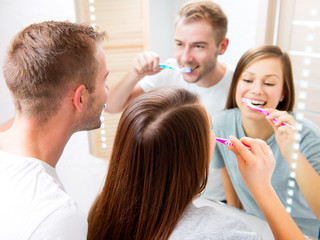 Young couple in the bathroom brushing teeth together