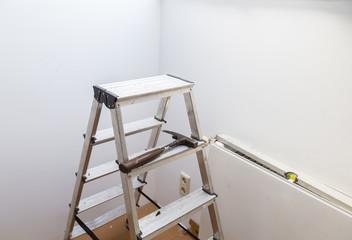 Leiter mit hammer und Wasserwaage für sanierung