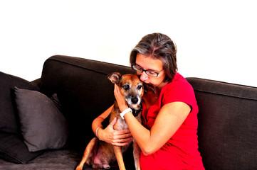 Woman cuddling with dog on a grey sofa