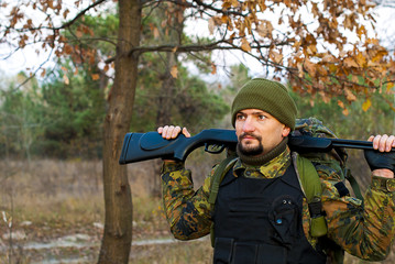 Soldier with a rifle in the autumn forest
