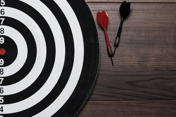 target and two darts on wooden background