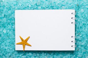 notepad and starfish on bath salt background
