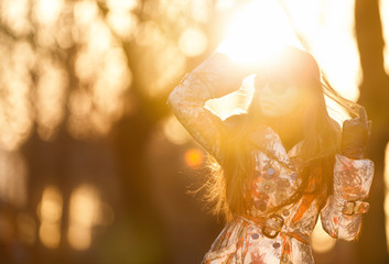 Young woman in the rays of the spring sun
