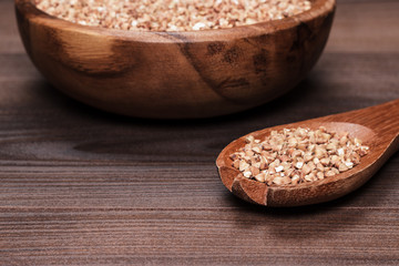 plate and spoon full of buckwheat over wooden background