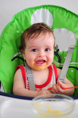 Smiling messy baby sitting in high chair holding spoon