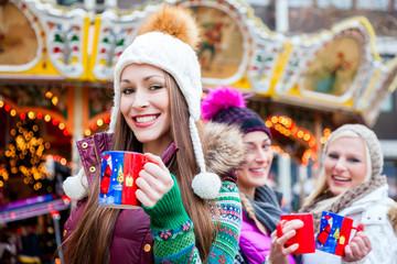 Frau trinkt Glühwein auf Weihnachtsmarkt