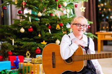 Mädchen spielt Gitarre an Heiligabend  zu Bescherung