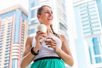Frau genießt Caffee to go in Dubai als Touristin