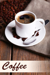 Cup of coffee and coffee beans on napkin on wooden background