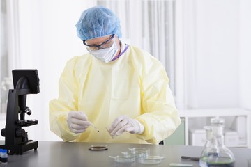 Scientist in protective gear with blood sample
