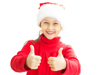 little girl in a Santa Claus hat shows two thumbs up on white is