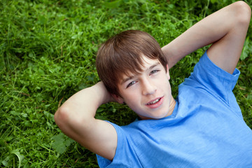 Happy teenager lying on grass in park