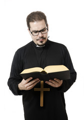 Isolated priest reading the bible
