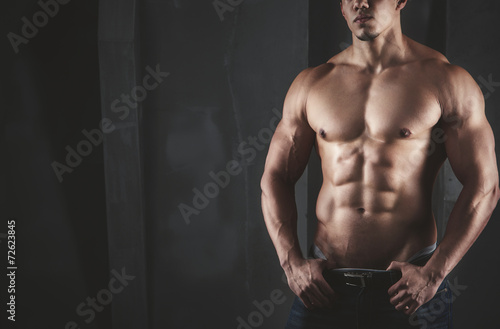 Leinwanddruck Bild Close up of young muscular man lifting weights