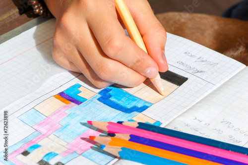 Child hand draws the multicolored minecraft picture. Outdoors cl