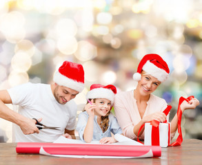 happy family in santa helper hats packing gift