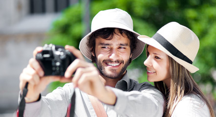 Smiling tourist showing photos to his girlfriend