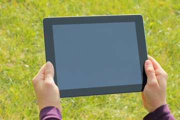 Woman hands holding tablet PC on green grass