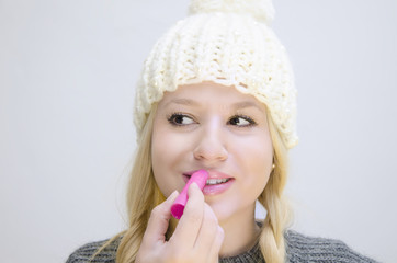 Cute girl white winter cap applying lip balm