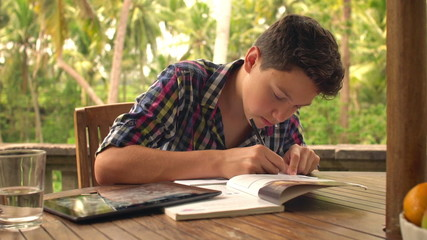 Young teenager doing homework, writing notes in notebook on terr