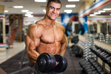 bodybuinder with dumbbell in gym